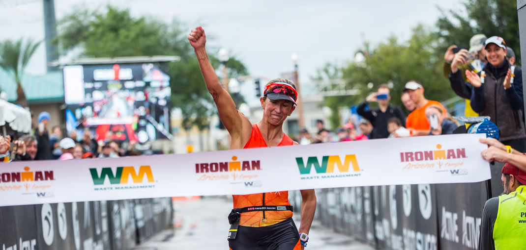 Meredith Kessler triathlete Ironman Arizona raising hand in victory