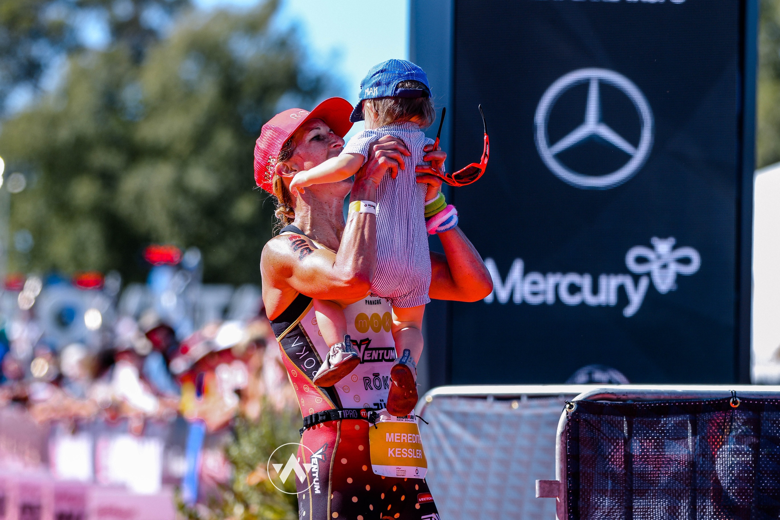 Meredith Kessler Professional Triathlete Finish Line 2019 Ironman New Zealand Holding son Mak Witsup Photo